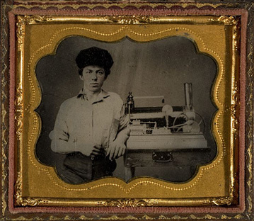 Unidentified young man, posed with model of steam driven engine on a table, ca. 1865